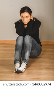 Sad woman sitting on floor and looking in camera. Emocional problems.