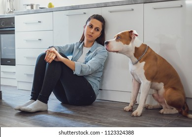 Sad woman sitting on a kitchen floor and looking at her dog