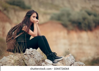 Sad Woman Sitting on a Rocky Cliff Terrified of Heights. Unhappy pensive depressed female backpacker crying