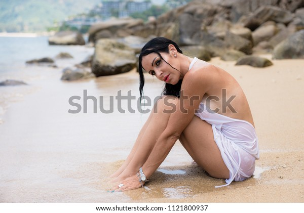 sad woman sitting on the sand beach against a sea landscape with stones and coastline