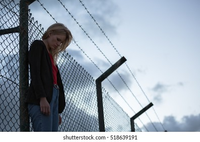 Sad woman standing alone against barbwire fence.