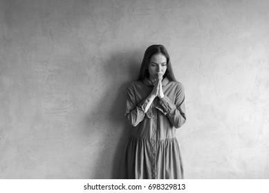 Sad woman standing beside the grunge wall