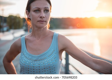 Sad woman standing by the water during sunset