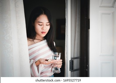 Sad woman taking pills   looks like be seriously sick with glass of water, Pharmaceutical medicament, cure in container for health, Antibiotic, Medicine and health care concept.