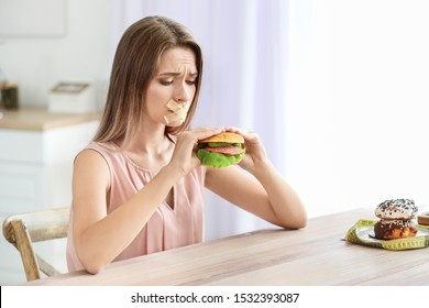Sad woman with taped mouth and with tasty burger in kitchen. Diet concept