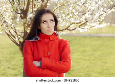 Sad Woman with Thermometer in Spring Blooming Decor - Portrait of a woman feeling sick surrounded by seasonal flowers