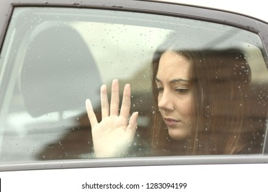 Sad woman touching window inside a car during a roadtrip a rainy day