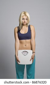 Sad woman unhappy or depressed with weight slimming scale