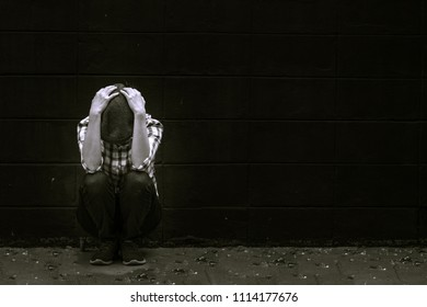 Sad woman use two hands holding her head and sitting on the floor has broken mirrors. She unhappy and strain because lose important things from life. Black and White Picture style.
