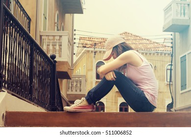 sad woman wearing a cap and hugging knees on stair, she is lonely most of the time, vintage tone
