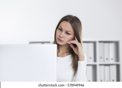 Sad woman in a white office is looking at her laptop screen. Bookshelves are seen in the background. Concept of not being satisfied with your work.