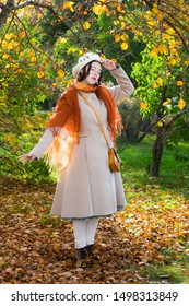 Sad women in a light coat and beret in the park on an autumn day