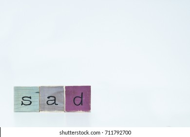 Sad. Wooden letters on white background