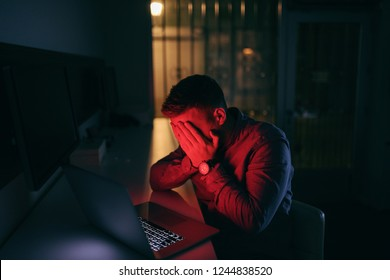 Sad worker holding head in hands while sitting in the office late at night.