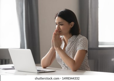 Sad worried asian female employee looking at laptop screen at office. Stressed upset manager stuck with hard task, thinking about correct difficult decision or hard problem solution, hoping for help.