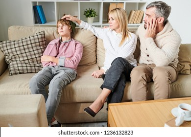 Sad worried parents in casual outfit puzzled about depression of teenage son who ignoring them, disappointed mother stroking head of son in living room