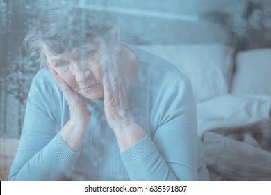 Sad, worried senior woman having memory disorder