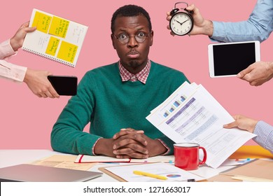 Sad young African American man dressed in green sweater, sits at desktop, hands with papers, alarm clock, touchpad, notepad with stickes, studies documentation, isolated over pink background