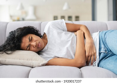 Sad young African American woman wearing casual clothes suffering from menstrual pain, feeling sick to her stomach, holding belly, having abdominal cramps during period and lying down on bed at home
