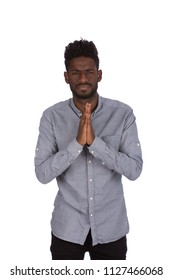 Sad young African man asking for forgiveness, praying hands sign and saying please, isolated on a white background.
