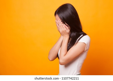 Sad young Asian  woman cry with palm to face on bright yellow background