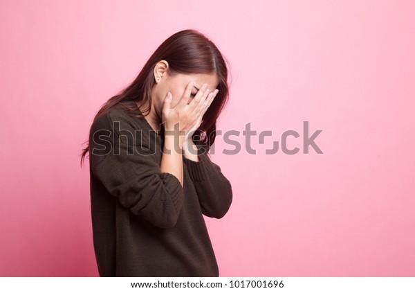 ピンクの背景に悲しいアジアの若い女性とヤシの顔の泣き声