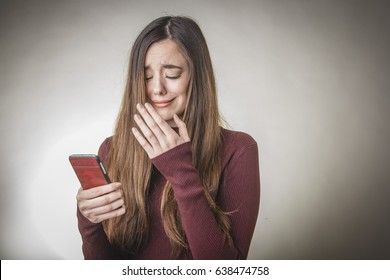 Sad young beautiful girl reading a message containing bad, terrifying news