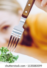 Sad young blonde woman dealing with anorexia nervosa or builimia having small green vegetable on plate. Dieting problems, eating disorder.