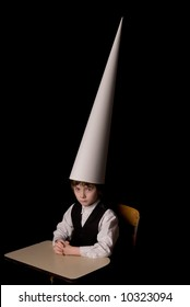 Sad young boy in a dunce cap at a school desk over a black background