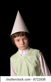 Sad young boy in a dunce cap over a black background