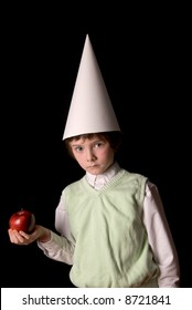 Sad young boy in a dunce cap with a red apple over a black background