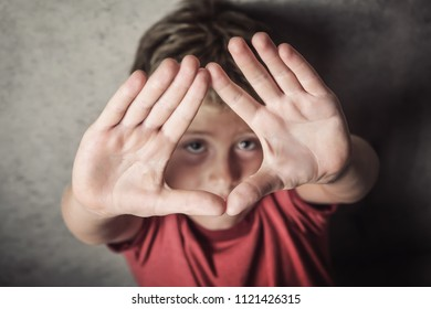 Sad young boy putting his hands up to protect himself, focus on hands