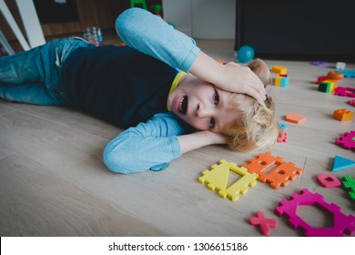 sad young boy shouting with toys scattered around, child in stress