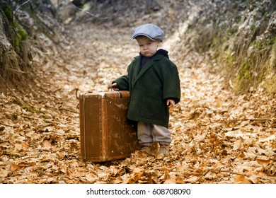 Sad young boy with suitcase is lonesome