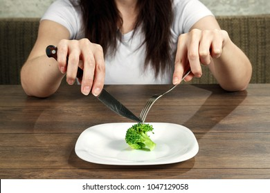sad young brunette woman dealing with anorexia nervosa or bulimia having small green vegetable on plate. Dieting problems, eating disorder.