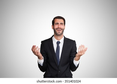Sad young business man with hands at shoulder level.