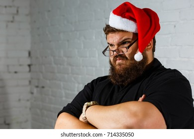 Sad young Caucasian man wearing casual t-shirt and red Santa Claus hat with white fur pouting, looking tired and bored, bearded man in santa hat