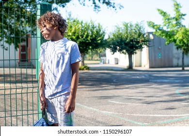 Sad young colored boy standing alone at gate at schoolyard.