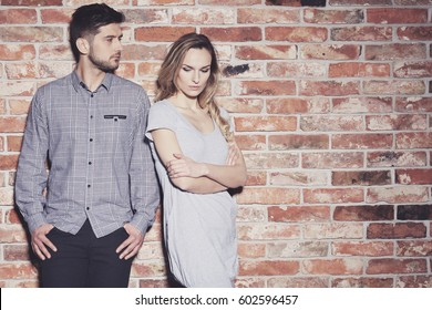Sad young couple arguing and standing against brick wall