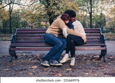 A sad young couple is embracing on a park bench in autumn