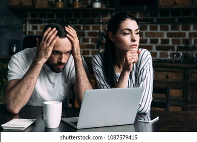 sad young couple sitting on kitchen with laptop and calculator