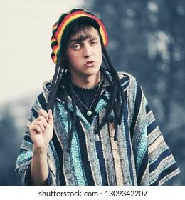Sad young fashion hippie man walking outdoor Stylish trendy model wearing rasta hat and poncho