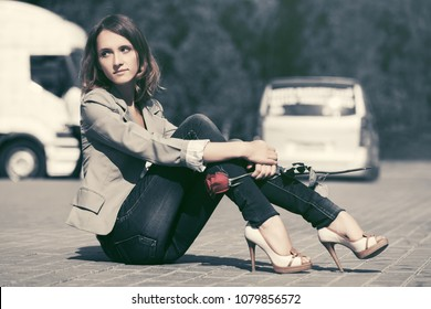 Sad young fashion woman with red rose sitting on the road Stylish female model in grey blazer and dark blue jeans