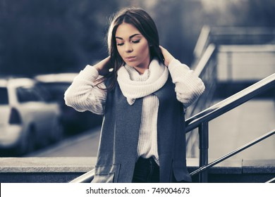 Sad young fashion woman walking in city street Stylish female model in long vest and white sweater outdoor