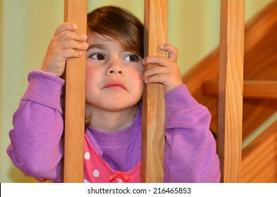 Sad young girl (age 4-5) looks at here fighting parents at home before bedtime.Concept photo of child, childhood, family, problems, divorce ,abuse, violence.Real people. Copy space
