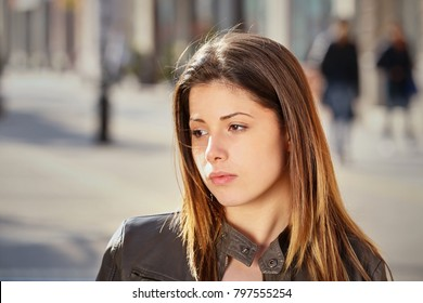 sad young girl alone on the street in spring