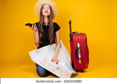 sad young girl goes on a journey, with a large suitcase, can not figure out the map