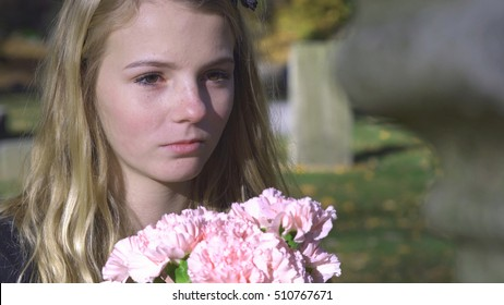 Sad young girl looking at gravestone holding flowers 4k