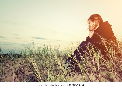 Sad young girl sitting alone on a grass outdoors,Sadness. Loneliness