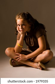 Sad young girl sitting down on floor with brown clothes and sandels